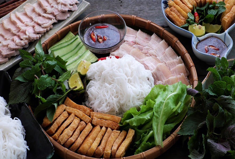 Delicious Vietnamese food, bun dau mam tom, is popular street food make from vermicelli with boiled meat, fried tofu, shrimp paste and green vegetables, cucumer and spice as chilli, lemon